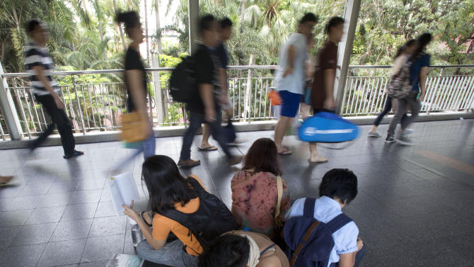 A group of anti-coup protestors read books along an elevated walkway during a protest in Bangkok, Thailand, Saturday, May 31, 2014. In junta-ruled Thailand where the army recently took power in a coup, the simple act of reading in public has become an act of resistance. (AP Photo/Sakchai Lalit)