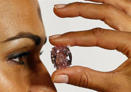 A model displays the 'Pink Star' 59.60 carat oval cut pink diamond at Sotheby's in Geneva September 25, 2013. The Pink Star will become the most expensive diamond ever when it goes into auction next November 13 with an asking price of $60 million. REUTERS/Ruben Sprich