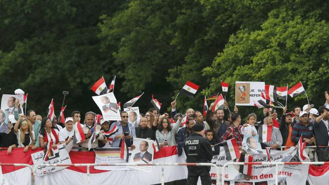 Supporters of Egypt's President Sisi wave on his arrival in front of Bellevue presidential palace in Berlin