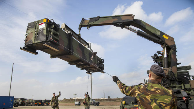 In this photo released by the Audio Visual Department of the Dutch Defense Ministry, Dutch military trucks carrying NATO's Patriot Missile Defense System to protect Turkey in case neighboring Syria launches an attack, are being unloaded at Incirnik base, near Adana, Turkey, Thursday, Jan. 24, 2013. The Dutch Patriot Systems and troops will ve stationed in Adana to prepare to operate a defensive missile system close to the border with Syria. (AP Photo/Rob van Eerden, Dutch Defense Ministry, HO)