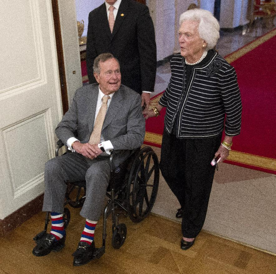 Former President George H.W. Bush, left, and his wife, former first lady Barbara Bush, arrive in the East Room of the White House in Washington, Thursday, May 31, 2012, for a ceremony to unveil the official portrait of their son former President George W. Bush. (AP Photo/Pablo Martinez Monsivais)