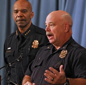 Denver Police Commander Ron Saunier, right, talks about the arrest of three suspects in the murder of five people and a fire at a Denver bar during a news conference at Denver Police Headquarters on Thursday, Oct. 18, 2012. Police Chief Robert White listens at left.(AP Photo/Ed Andrieski)