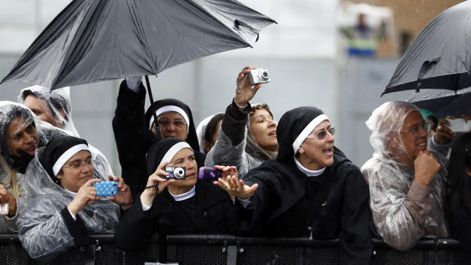 Nuns wave at and takes pictures of Pope Francis as he drives by in his popemobile as he leaves Aparecida, Brazil, Wednesday, July 24, 2013. Tens of thousands of faithful flocked to the tiny town of Aparecida, tucked into an agricultural region halfway between Rio de Janeiro and Sao Paulo, where he is celebrated the first public Mass of his trip in a massive basilica dedicated to the nation's patron saint. (AP Photo/Victor R. Caivano)