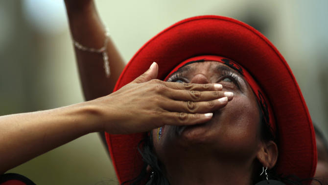 A supporter of Venezuela's acting President Nicolas Maduro gestures as she listens to acting President Nicolas Maduro speak outside the national electoral council after he registered his candidacy for president to replace Hugo Chavez in Caracas, Venezuela, Monday, March 11, 2013.  Presidential elections were announced to take place on April 14, after Maduro announced on March 5 that Chavez had died. (AP Photo/Rodrigo Abd)
