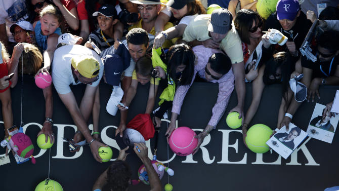 Switzerland's Roger Federer signs autographs as he leaves Rod Laver Arena following his first round win over France's Benoit Paire at the Australian Open tennis championship in Melbourne, Australia, Tuesday, Jan. 15, 2013. (AP Photo/Andy Wong)