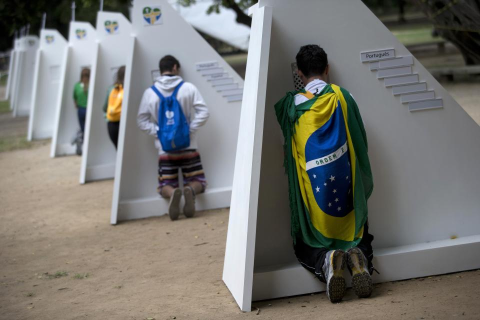 Catholics kneel at portable confessionals set up in Quinta da Boa Vista park during World Youth Day events in Rio de Janeiro, Brazil, Tuesday, July 23, 2013. As many as 1 million young people from around the world are expected in Rio for the Catholic youth event. (AP Photo/Silvia Izquierdo)