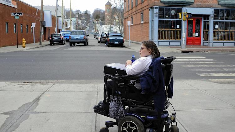 In this photo taken Friday, March 1, 2013, Jennifer Lortie begin her two-hour commute home after work, waiting for a bus in Willimantic, Conn. Of the 29 million working–age Americans with a disability Lortie, who has limited arm and leg use due to cerebral palsy, is one of the 5.1 million disabled Americans who are actually employed. The National Council on Disability's Jeff Rosen says long-standing prejudicial attitudes need to be addressed to boost jobs. (AP Photo/Jessica Hill)