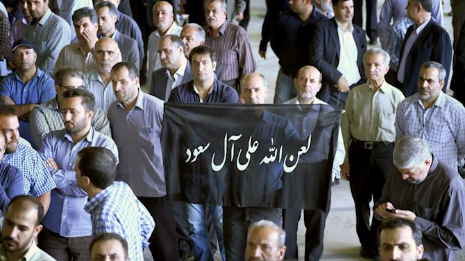 """A man holds a banner that reads """"God's curse on Al Saud (Saudi royal family)"""" during the funeral of victims killed in Saudi Arabia in a stampede at the haj pilgrimage, in Tehran"""