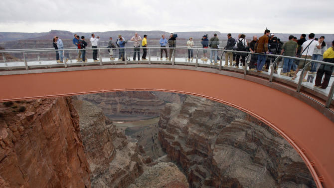 FILE - In this file photo taken Tuesday, March 20, 2007, people walk on the Skywalk during the First Walk event at the Grand Canyon on the Hualapai Indian Reservation at Grand Canyon West, Ariz.  The Skywalk opened to the general public on March 28, 2007. A federal court has upheld a $28 million judgment against a business arm of the northern Arizona tribe that owns the Grand Canyon Skywalk. The American Arbitration Association had awarded Las Vegas businessman David Jin the money in August. His attorneys went to federal court to enforce it. Jin invested $30 million to build the Skywalk, a glass bridge that gives visitors a view of the Colorado River from the Hualapai reservation. (AP Photo/Ross D. Franklin, File)