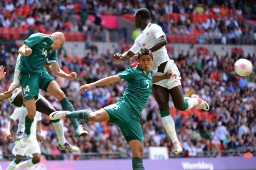 Senegal's Moussa Konate (R) challenges Mexico's Jorge Enriquez (L) and Darvin Chavez (C) for the ball