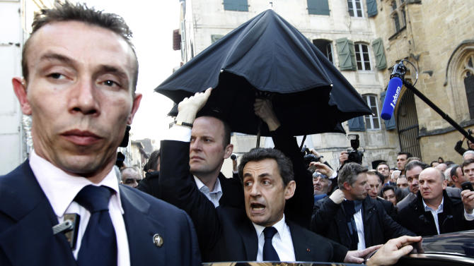 French President Nicolas Sarkozy, center, waves as he enters his car surrounded by security staff, in Bayonne, southwesternFrance, Thursday, March 1, 2012. Sarkozy, who is campaigning for reelection, took refuge in a cafe Thursday after a crowd in the Basque city of Bayonne became boisterous, reproaching the socialist party and Basque separatists of working together to disrupt his visit. (AP Photo/Bob Edme)