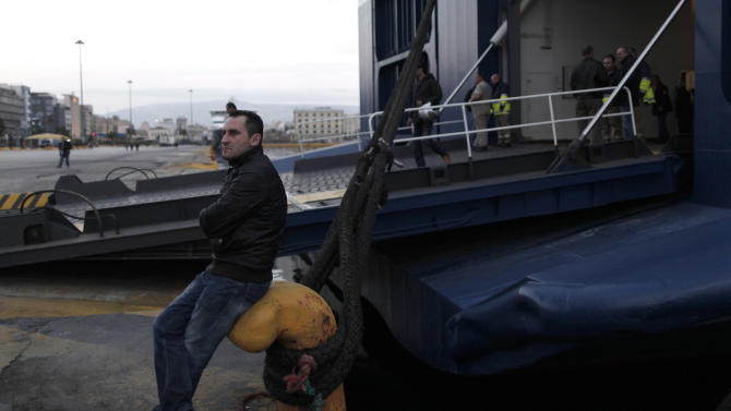 FILE - In this Tuesday, Feb. 5, 2013 file photo, an unpaid striking dock worker sits next to an idle ferry, at the port of Piraeus, near Athens. Researchers from Greece's largest labor union, the GSEE, say the country's three-year crisis has left nearly two-thirds of private sector employees without receiving their regular salaries. GSEE has called a general strike for Wednesday Feb. 20. (AP Photo/Petros Giannakouris, File)