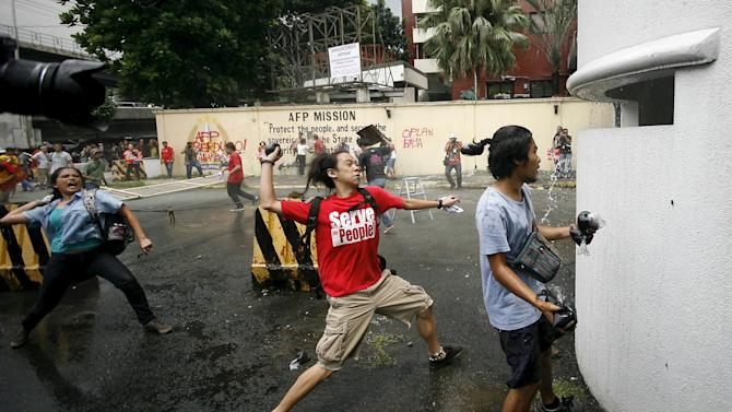 Youth activists throw paint bombs at the gates of the Armed Forces of the Philippines outside their headquarters in Camp Aguinaldo, Quezon City, metro Manila