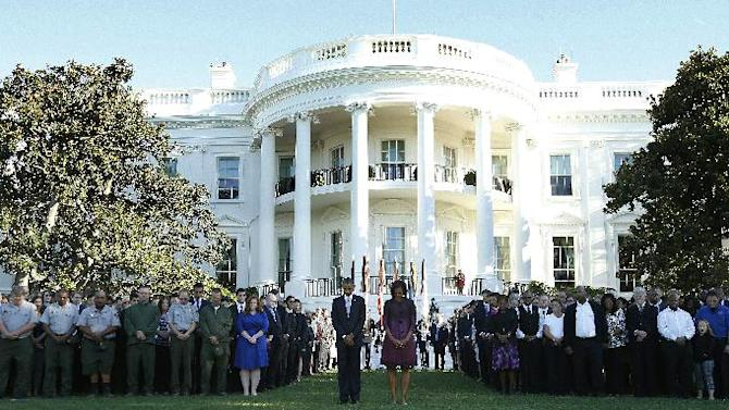 President Barack Obama and first lady Michelle Obama join members of the White House staff during a moment of silence to mark the 11th anniversary of the Sept, 11th, Tuesday Sept. 11, 2012, on the South Lawn of the White House in Washington. (AP Photo/Carolyn Kaster)