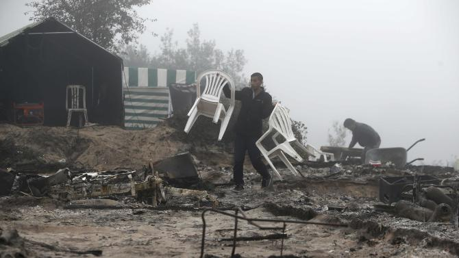 """A migrant carries chairs as he walks through the charred debris from makeshift shelters and tents in the """"Jungle"""" on the third day of their evacuation and transfer to reception centers in France, as part of the dismantlement of the camp in Calais"""