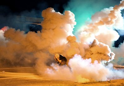 CLICK IMAGE for slideshow: A protester takes shelter from smoke billowing around him Wednesday, Aug. 13, 2014, in Freguson, Mo. Protests in the St. Lo...