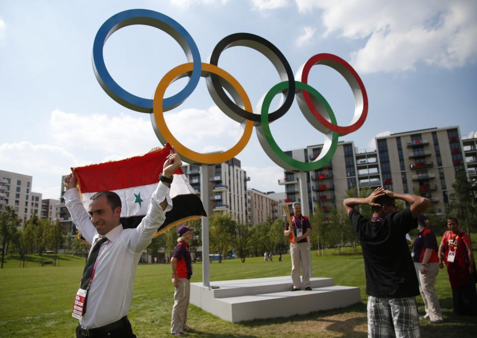 Tony Ashour, left, of Syria, poses with a flag as he visits the Athletes' Village at the Olympic Park, Wednesday, July 25, 2012, in London. Opening ceremonies for the 2012 London Olympics will be held Friday, July 27. (AP Photo/Jae C. Hong, Pool)