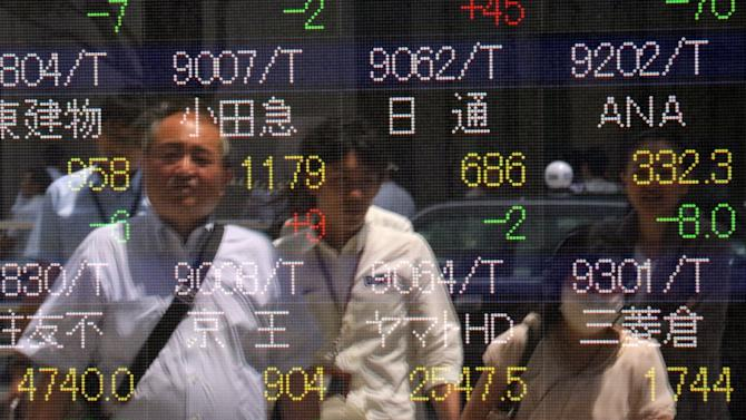 Pedestrians are reflected on a share prices board in Tokyo on June 2, 2015