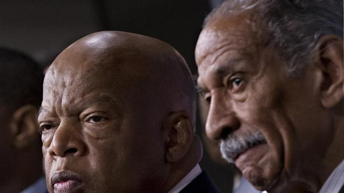 Rep. John Lewis, D-Ga., left, and Rep. John Conyers, D-Mich., right, co-chairs of the Civil Rights Taskforce of the Congressional Black Caucus, join other members of the House to express disappointment in the Supreme Court's decision on Shelby County v. Holder that invalidates Section 4 of the Voting Rights Act, Tuesday, June 25, 201, on Capitol Hill in Washington. Lewis, a prominent activist in the Civil Rights Movement in the 1960's, recalled being attacked and beaten trying to help people in Mississippi to register and vote in the 1960's. (AP Photo/J. Scott Applewhite)