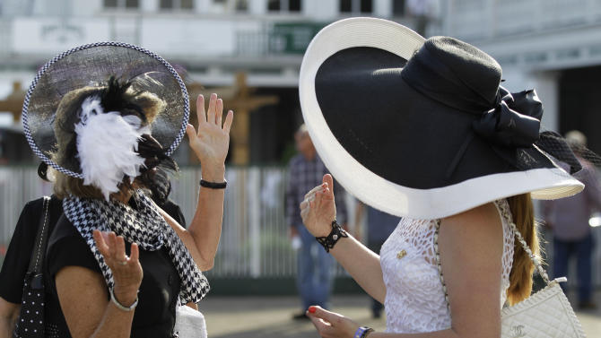 Dawn Paden, left, from Mountain Home, Ark., chats with Carrie Cooke, of Louisville, Ky., before the 138th Kentucky Derby horse race at Churchill Downs Saturday, May 5, 2012, in Louisville, Ky. The Run for the Roses draws them to Churchill Downs. But what race goers wear is as much a spectacle in itself. (AP Photo/Mark Humphrey)