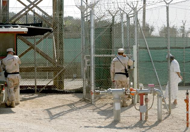 GUANTANAMO BAY, CUBA - MAY 09:  (IMAGE REVIEWED BY U.S. MILITARY PRIOR TO TRANSMISSION)  Two members of the U.S. Military stand near a detainee at Camp 4 inside of Camp Delta May 9, 2006 in Guantanamo