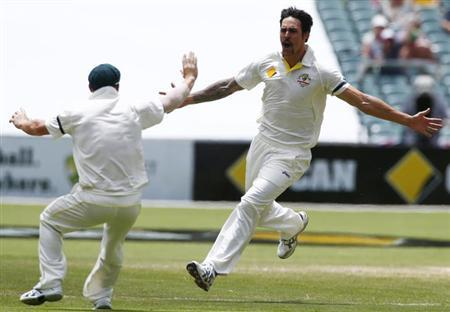 Australia's Mitchell Johnson (R) celebrates with David Warner after taking the wicket of England's Stuart Broad during the third day's play in the second Ashes cricket test at the Adelaide