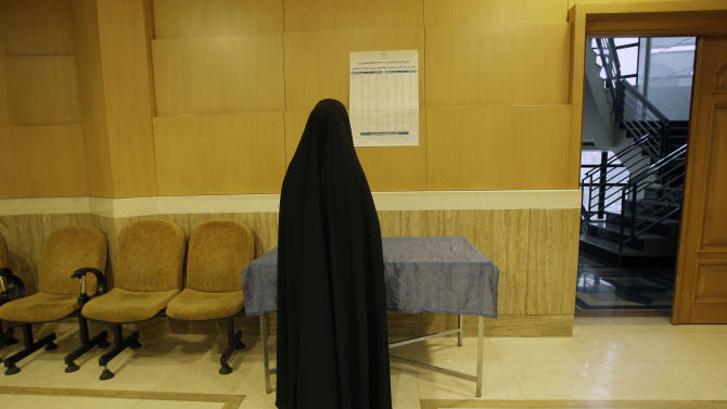 A head-to-toe veiled Iranian woman checks the list of the candidates in the parliamentary runoff elections at a polling station in Tehran, Iran, Friday, May 4, 2012. The country has begun runoff elections for more than one-fifth of parliamentary seats. Friday's report says 130 hopefuls will compete for 65 seats in 33 constituencies including the capital Tehran with 25 undecided seats. (AP Photo/Vahid Salemi)