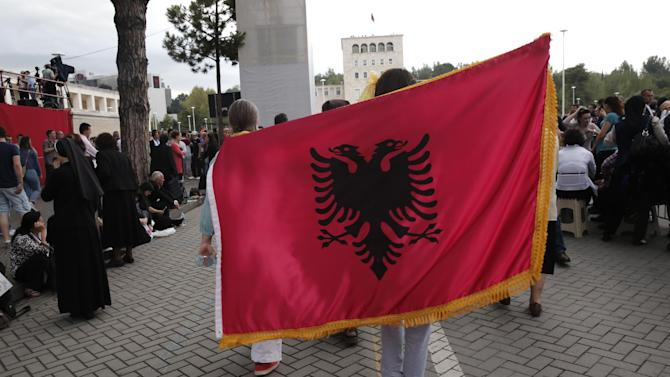 "Faithful hold an Albanian flag on their way to Mother Teresa Square, in Tirana, Sunday, Sept. 21, 2014. Pope Francis denounced how extremists around the world are ""perverting"" religion to justify violence as he arrived Sunday in Albania, a Balkan nation where Christians and Muslims endured brutal religious oppression under communism but today live and work together peacefully. (AP Photo/Petros Giannakouris)"