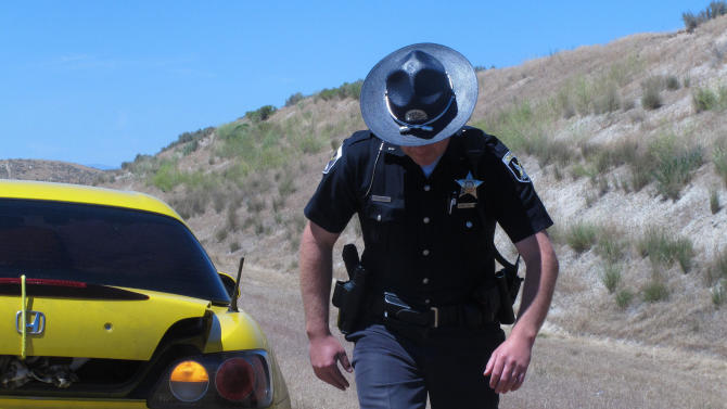 In this photo taken June 20, 2012, Idaho State Police Trooper Justin Klitch walks away from a car he stopped on the Idaho-Oregon border in Fruitland, Idaho.  As the Evergreen state works out the various complications of its new law,  including the fact that marijuana is still illegal under federal law, neighbors of Washington are watching with curiosity, and perhaps some apprehension. Idaho officials already have their hands full with Idahoans obtaining medical marijuana cards out of state. The Gem State borders three medical marijuana states, a reality that has caused medical marijuana arrests to outpace those of traffickers or other users. Although Idaho is a largely conservative state, there are pockets defined by borders and demographics that could create new challenges for law enforcement.  (AP Photo/Nigel Duara)
