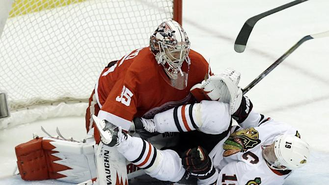 Chicago Blackhawks center Jonathan Toews (19) crashes into Detroit Red Wings goalie Jimmy Howard (35) during the second period in Game 4 of the Western Conference semifinals in the NHL hockey Stanley Cup playoffs in Detroit, Thursday, May 23, 2013. (AP Photo/Paul Sancya)