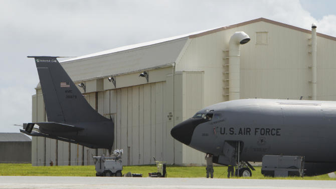 In this Aug. 14, 2012 photo, a ground crew member works below a U.S. Air Force KC-135 Stratotanker, as another KC-135 is seen in a hanger behind, at Kadena Air Base on Japan's southwestern island of Okinawa. The most recent of the KC-135 refueling tankers currently in service started flying in 1964. For decades, the U.S. Air Force has grown accustomed to such superlatives as unrivaled and unbeatable. Now some of its key aircraft are being described with terms like decrepit.  (AP Photo/Greg Baker)