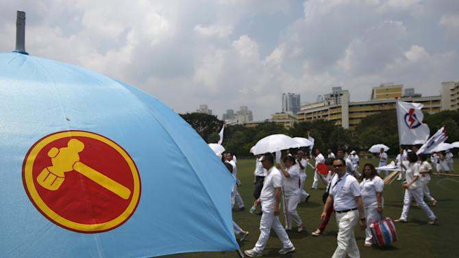 People's Action Party (PAP) supporters pass a Workers' Party supporter carrying an umbrella at a nomination center ahead of the general elections in Singapore