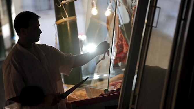 A butcher prepares meat for customers in a local market in central Athens
