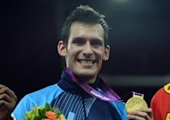 Argentina&#39;s Sebastian Eduardo Crismanich poses with his gold medal on the podium during the victory ceremony of the men&#39;s  taekwondo  under 80 kg  category  of the London 2012 Olympic games, on August 10, 2012 at the ExCel centre in London. AFP PHOTO / TOSHIFUMI KITAMURA