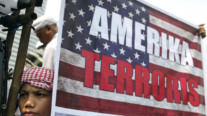 A Muslim youth pauses near a poster during a protest  against an anti-Islam film in Jakarta, Indonesia, Monday, Sept. 17, 2012. Indonesians enraged over an anti-Islam film hurled rocks and Molotov cocktails at the U.S. Embassy in Jakarta on Monday, marking the first violence in the world's most populous Muslim country since outrage exploded last week in the Middle East and beyond. (AP Photo/Dita Alangkara)