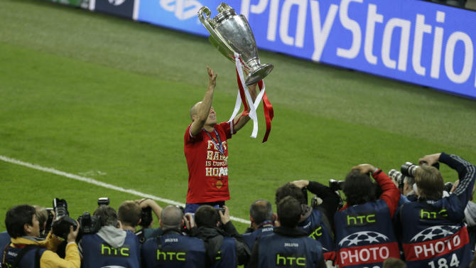 Bayern's Arjen Robben of the Netherlands tosses the trophy into the air after winning the Champions League Final soccer match between  Borussia Dortmund and Bayern Munich at Wembley Stadium in London, Saturday May 25, 2013. (AP Photo/Alastair Grant)