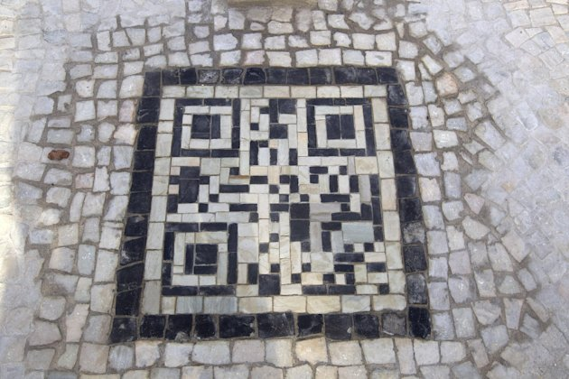 A two-dimensional bar code, or QR code, as they're known, made from black and white stones covers a sidewalk near the beach in Rio de Janeiro, Brazil, Friday, Jan. 25, 2013. The QR codes are being pla