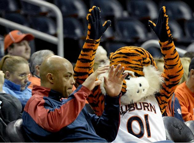 Former NBA standout and Auburn alumni Charles Barkley, left, and Auburn's mascot watch the second half of an NCAA college basketball game against Illinois on Sunday, Dec. 8, 2013, in Atlanta