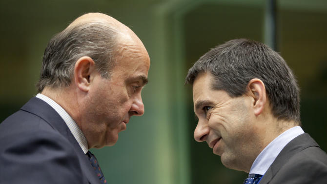 Spain's Economy Minister Luis de Guindos, left, speaks with Portugal's Finance Minister Vitor Gaspar during a meeting of EU finance ministers in Brussels on Wednesday, Dec. 12, 2012. European Union finance ministers on Wednesday sought to agree on the creation of a single supervisor for banks across the 27-country bloc after France and Germany apparently patched up their differences over the issue. (AP Photo/Virginia Mayo)