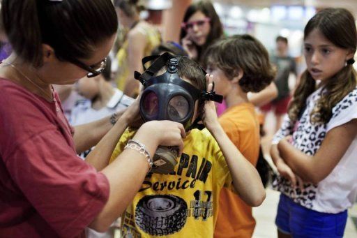 An Israeli boy receives help to fit a gas mask at a distribution centre in a shopping center in Mevaseret Zion on the outskirts of Jerusalem on July 25. A high-volume public debate in Israel over a possible imminent military strike on Iran's nuclear facilities is designed to pressure Washington to back its ally more firmly, experts say