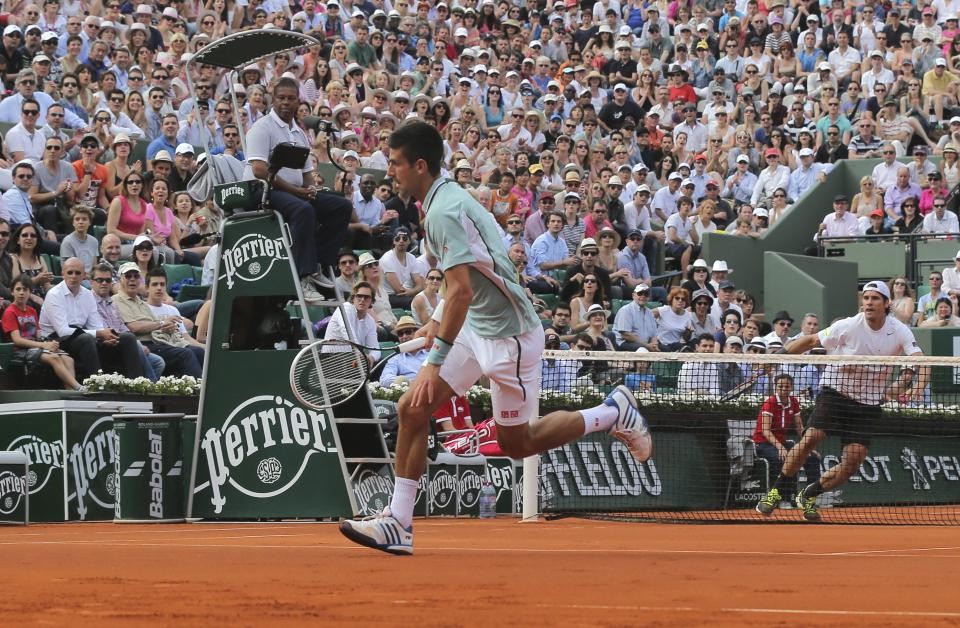 Serbia's Novak Djokovic runs to return the ball to Germany's Tommy Haas, right, during their quarterfinal match of the French Open tennis tournament at the Roland Garros stadium Wednesday, June 5, 2013 in Paris. (AP Photo/Michel Euler)