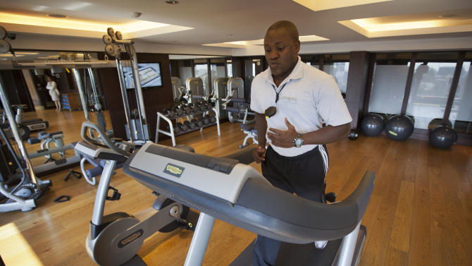 In this photo taken Wednesday, Sept. 26, 2012, a fitness trainer exercises in the gym of the Sankara Nairobi hotel in Nairobi, Kenya. International hotel developers are planning nearly 40,000 new rooms across Africa in the coming years, the continent's business travel is increasing, and Africa's middle class will soon begin leisure travel en masse. (AP Photo/Ben Curtis)