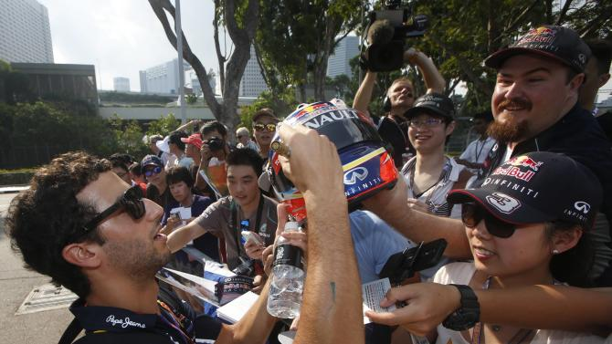 Red Bull Formula One driver Ricciardo of Australia signs autographs as he arrives ahead of the first practice session of the Singapore F1 Grand Prix at the Marina Bay street circuit in Singapore