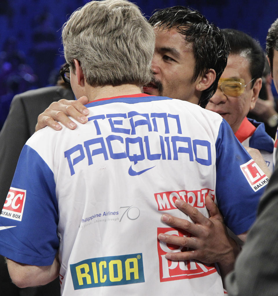 Manny Pacquiao, from the Philippines, right, whispers in the ear of his trainer Freddie Roach following his split decision loss to Timothy Bradley, from Palm Springs, Calif., in their WBO welterweight title fight Saturday, June 9, 2012, in Las Vegas. (AP Photo/Julie Jacobson)