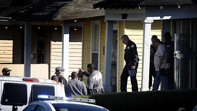 Memphis Police investigate the scene where an officer was shot when another officer tried to shoot a pit bull during the search of a home Thursday, Nov. 8, 2012 while attempting to serve a search warrant on the 500 block of Arrington in North Memphis, Tenn. The officer was transported to the Regional Medical Center at Memphis. (AP Photo/The Commercial Appeal, Mark Weber)