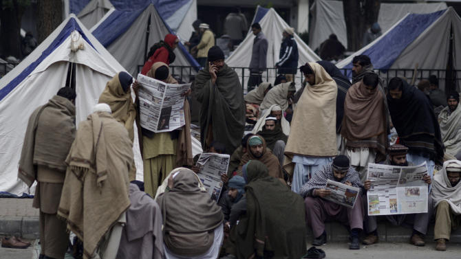 Supporters of Pakistani Sunni Muslim cleric Tahir-ul-Qadri, gather outside their tents, as they camp near the parliament, during an anti-government rally in Islamabad, Pakistan, Thursday, Jan. 17, 2013. Several thousand protesters shouting anti-military slogans displayed the bodies of 15 local villagers in northwestern Pakistan, claiming they were shot dead in their homes by security forces in an overnight raid. Hours later, police dispersed the protesters using water cannons and tear gas. (AP Photo/Muhammed Muheisen)