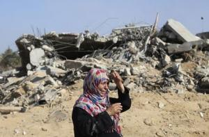 A Palestinian woman reacts upon seeing her house in …