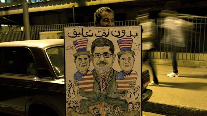 """An Egyptian protester holds a poster depicting Egyptian President Mohammed Morsi, center, holding his two sons, with the colors of the American flag and Arabic writing that reads, """"with no comment,"""" during a march marking the first anniversary of 26 Coptic Christians killed during an anti-government demonstration, in front of the National State T.V. building, known as Maspero, in Cairo, Egypt, Tuesday, Oct. 9, 2012. Muslim clerics, Christian priests, activists and former liberal lawmakers were among those marching to mark the anniversary of the """"Maspero massacre,"""" referring to the name of the state TV building, where the clashes broke out a year ago. (AP Photo/Khalil Hamra)"""