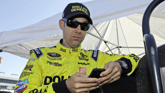 Matt Kenseth checks his phone prior to practice for Denny Hamlin's Charity Race at Richmond International Raceway in Richmond, Va., Thursday, April 25, 2013. The driver for Joe Gibbs Racing spoke out Thursday, one day after his team was slapped with some of the harshest penalties in NASCAR history because his race-winning car at Kansas last week failed post-race inspection. (AP Photo/Steve Helber)