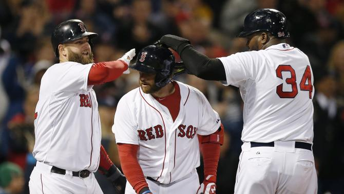 Boston Red Sox's David Ortiz (34) and Mike Napoli, left, celebrate after scoring a on a three-run home run by Jonny Gomes, center, in the sixth inning of a baseball game against the Baltimore Orioles in Boston, Sunday, April 20, 2014. (AP Photo/Michael Dwyer)